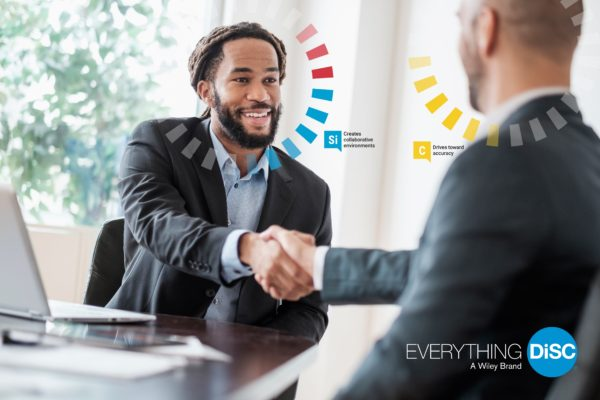 Two men shaking hands after a business deal with their disc personality traits highlighted above them